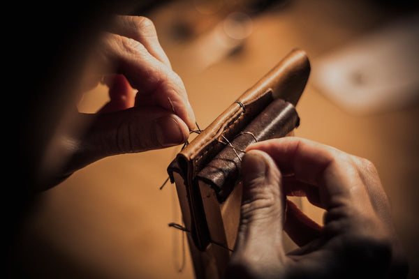 Image of Matt Nesbitt from Colville Leather hand-stitching his handmade leather wallets