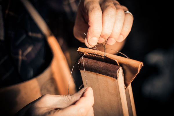 Image of Matt Nesbitt from Colville Leather hand-stitching a handmade leather wallet