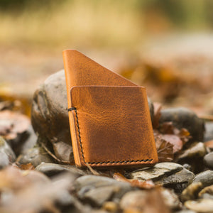 handmade leather wallet, pebbles and leaves