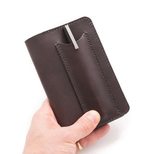 Hand holding a leather notebook cover with a pen pocket on the front