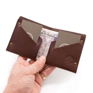 Leather bifold wallet holding money and cards