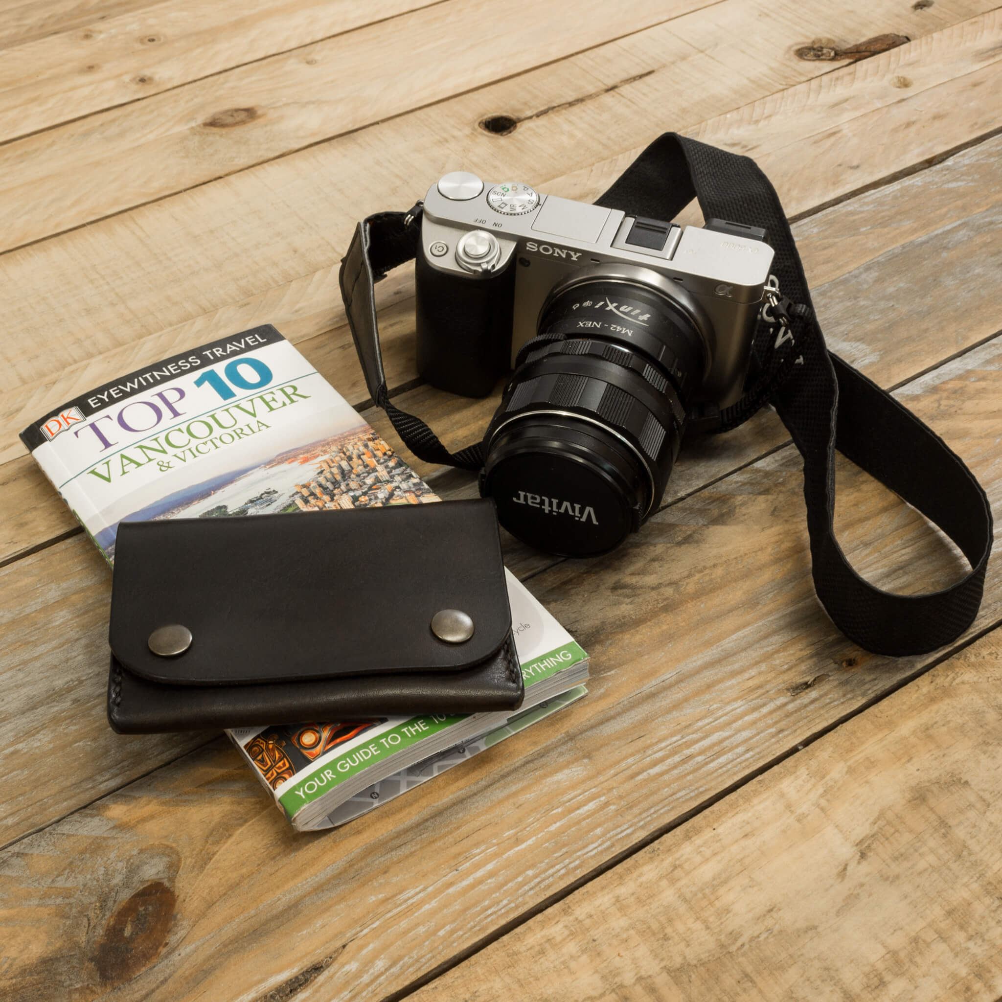 SLR camera and map with handmade leather wallet