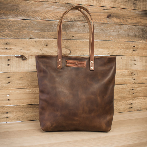 handmade leather tote bag on wooden bench