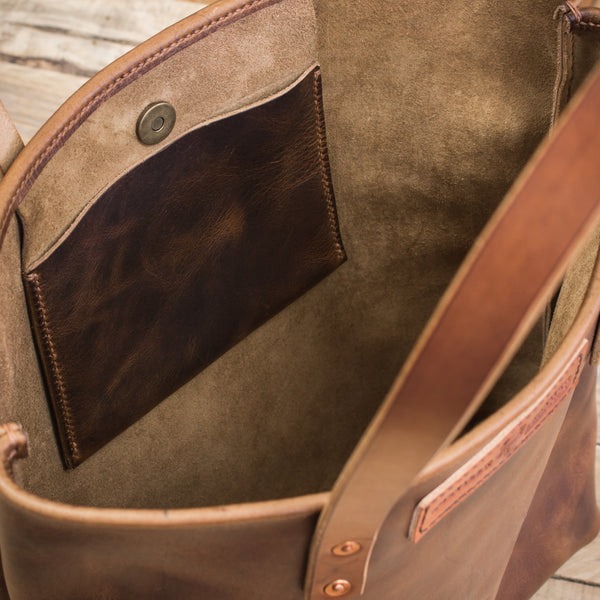 handmade leather tote bag close up of interior pocket and metal clasp