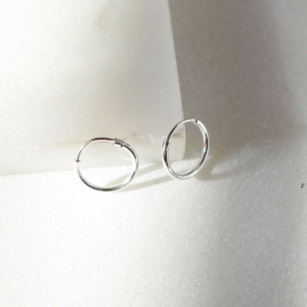 Sterling Silver huggie hoop that's minimal and dainty. Small, silver hoop.