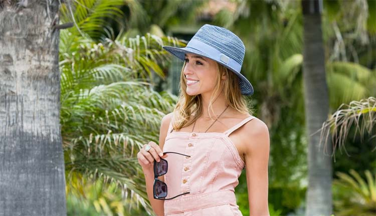 introducing carkella hats made for golf and travel for snowbirds. women wearing navy blue carkella sydney fedora with magnetic ball marker. setartrading hat shop