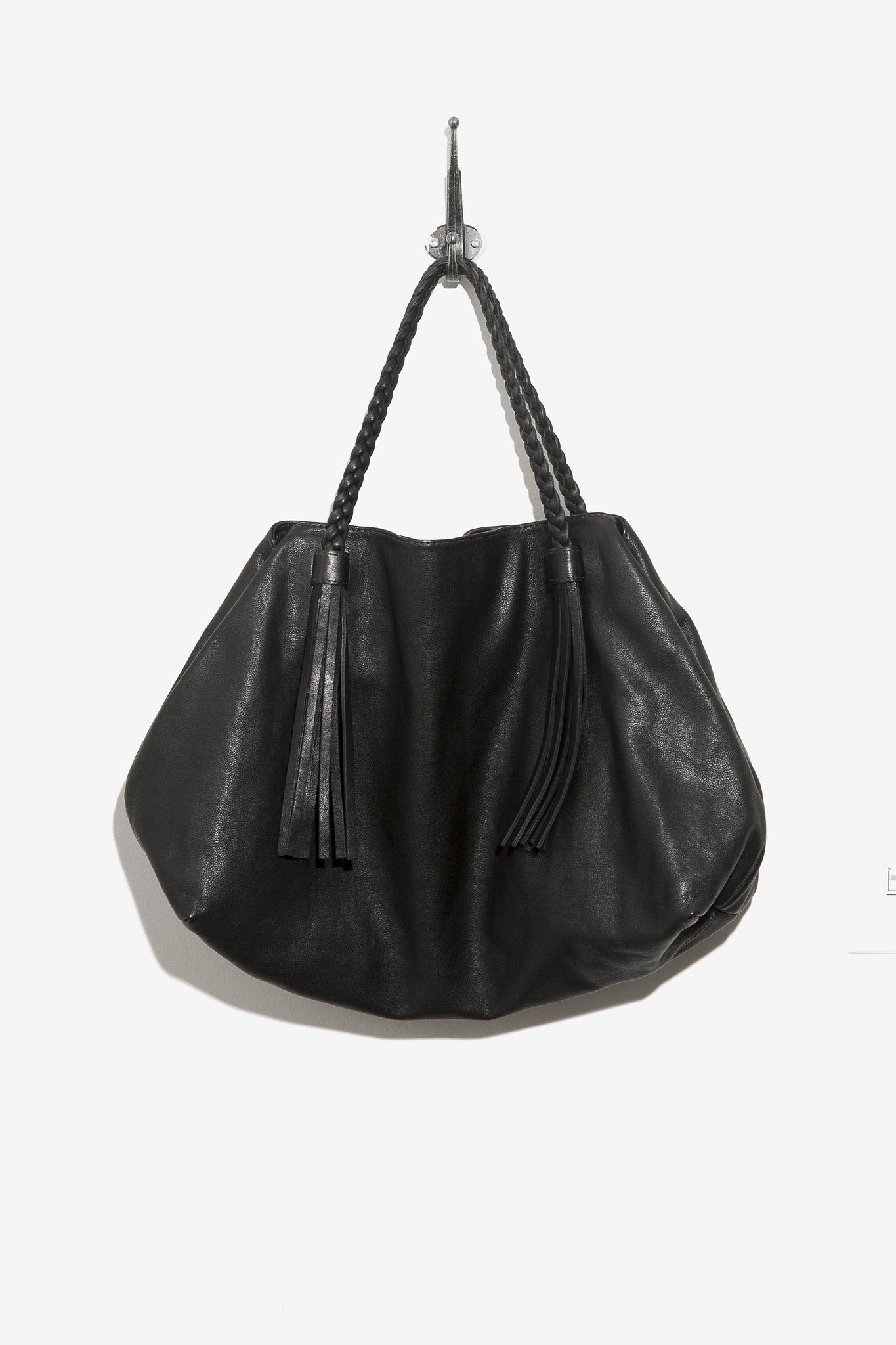 Tote Bag is a black tote with braided straps and tassel features designed by Moses Nadel.