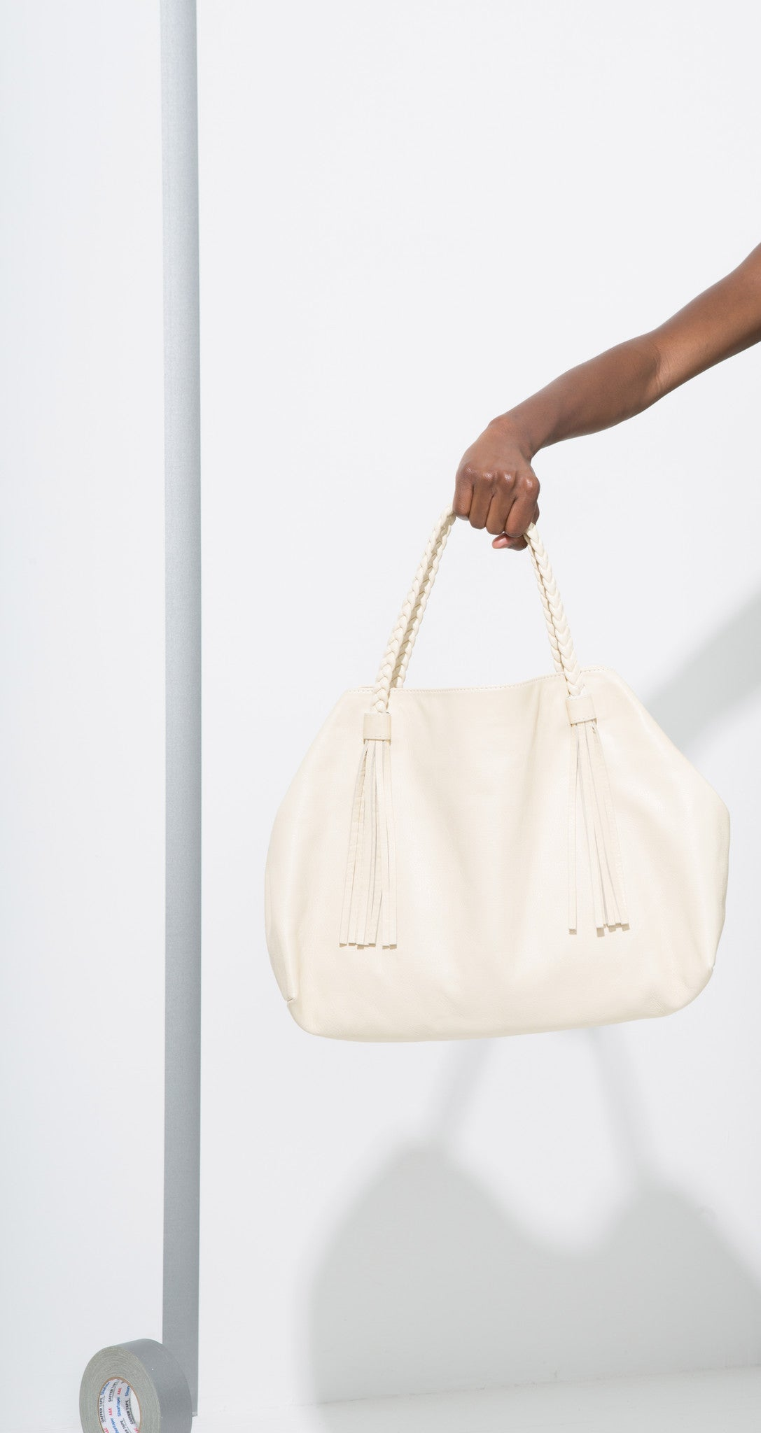 Tote Bag is a cream tote with braided straps and tassel features designed by Moses Nadel.