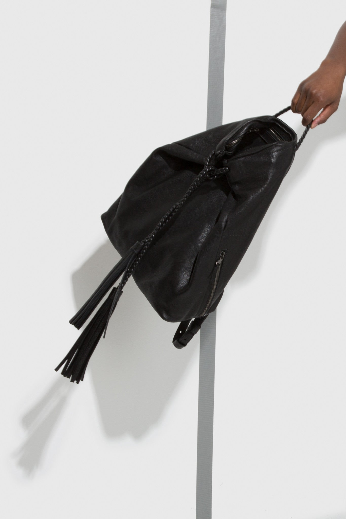 Tassel Backpack is a black leather backpack with tassel with braided straps and leather tassels designed by Moses Nadel.