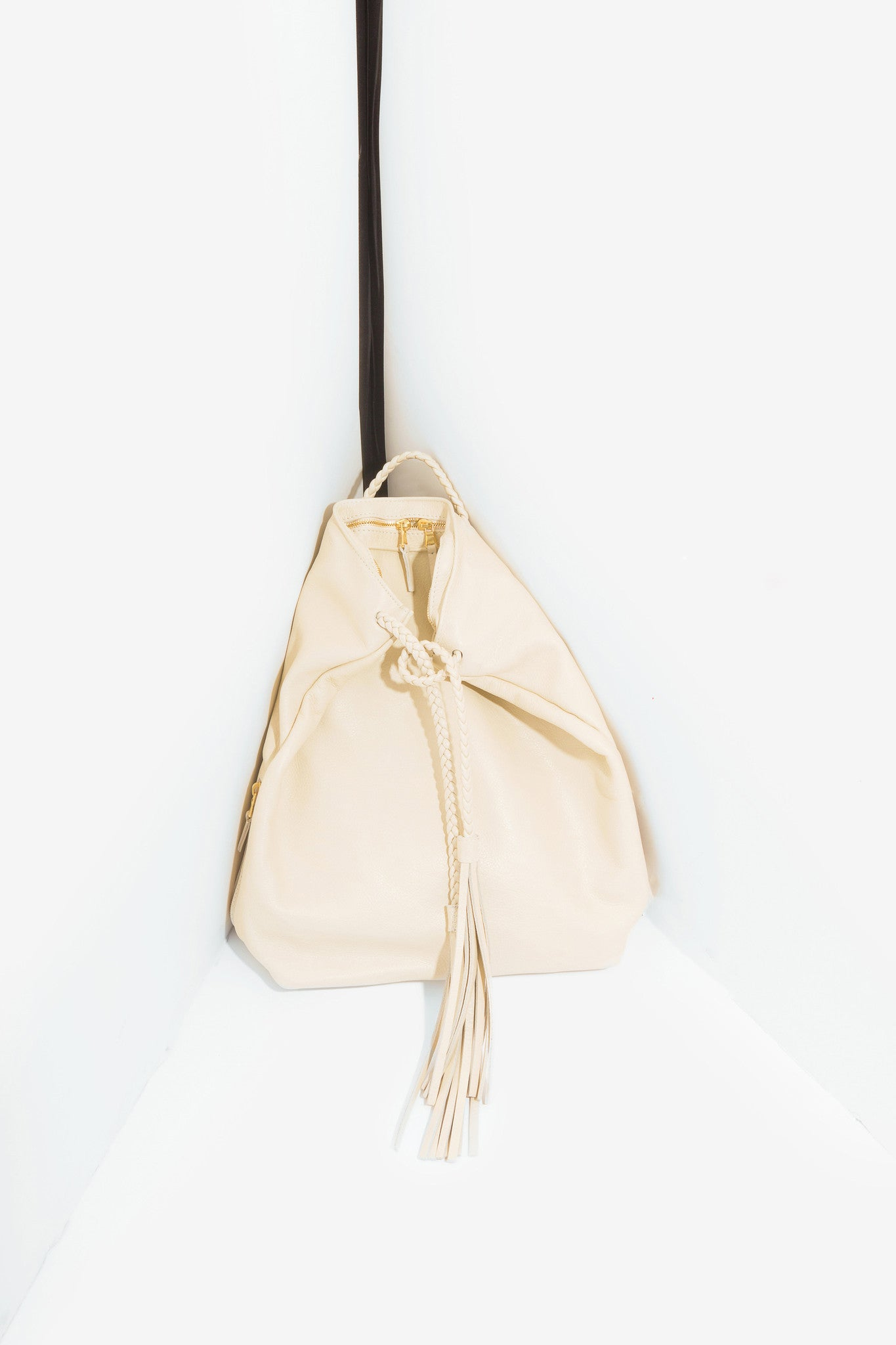 Tassel Backpack is a cream leather backpack with tassel with braided straps and leather tassels designed by Moses Nadel.