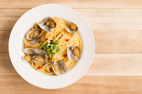 Pasta with clams on a wooden background.
