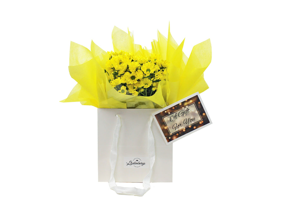 Flowers in yellow presented in a white gift bag delivered within Auckland NZ