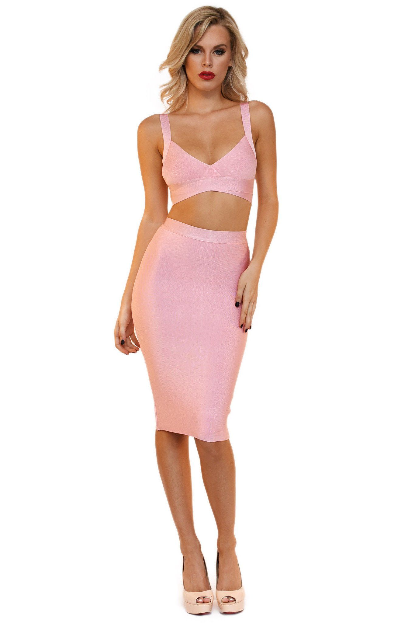 Front of pink two piece bandage set including a bralette style top with cutouts and a midi pencil skirt