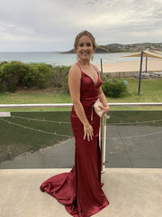Noodz Boutique's customer wearing Electra sleeveless satin evening gown with deep v neckline, lace up back design, front left high split and long train