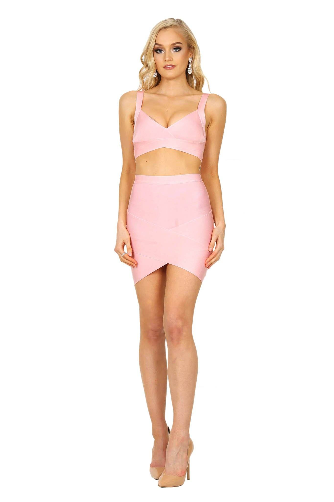 Pink matching fitted bandage set including bralette style top and arched hem mini skirt