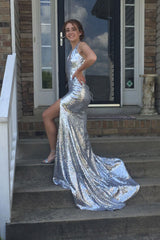 Customer wearing silver Estellina sequin sleeveless evening long gown with deep V neckline, thigh-high slit, halter-neck strings, open back, and long train