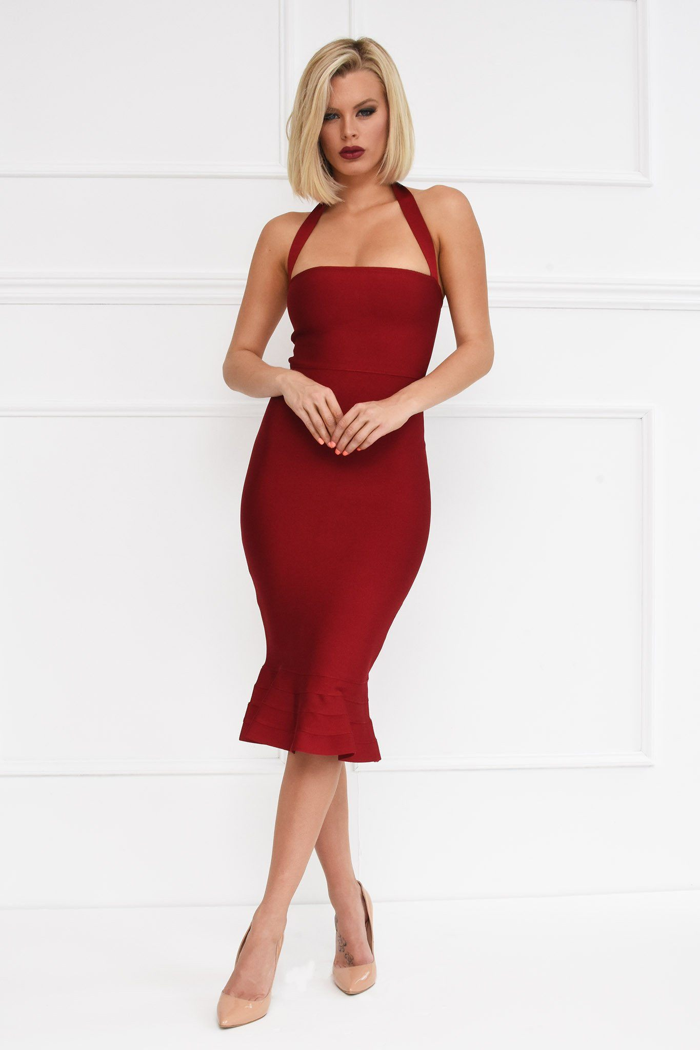 Front shot of wine red colored midi bodycon bandage dress with fluted ruffle hem and halterneck design
