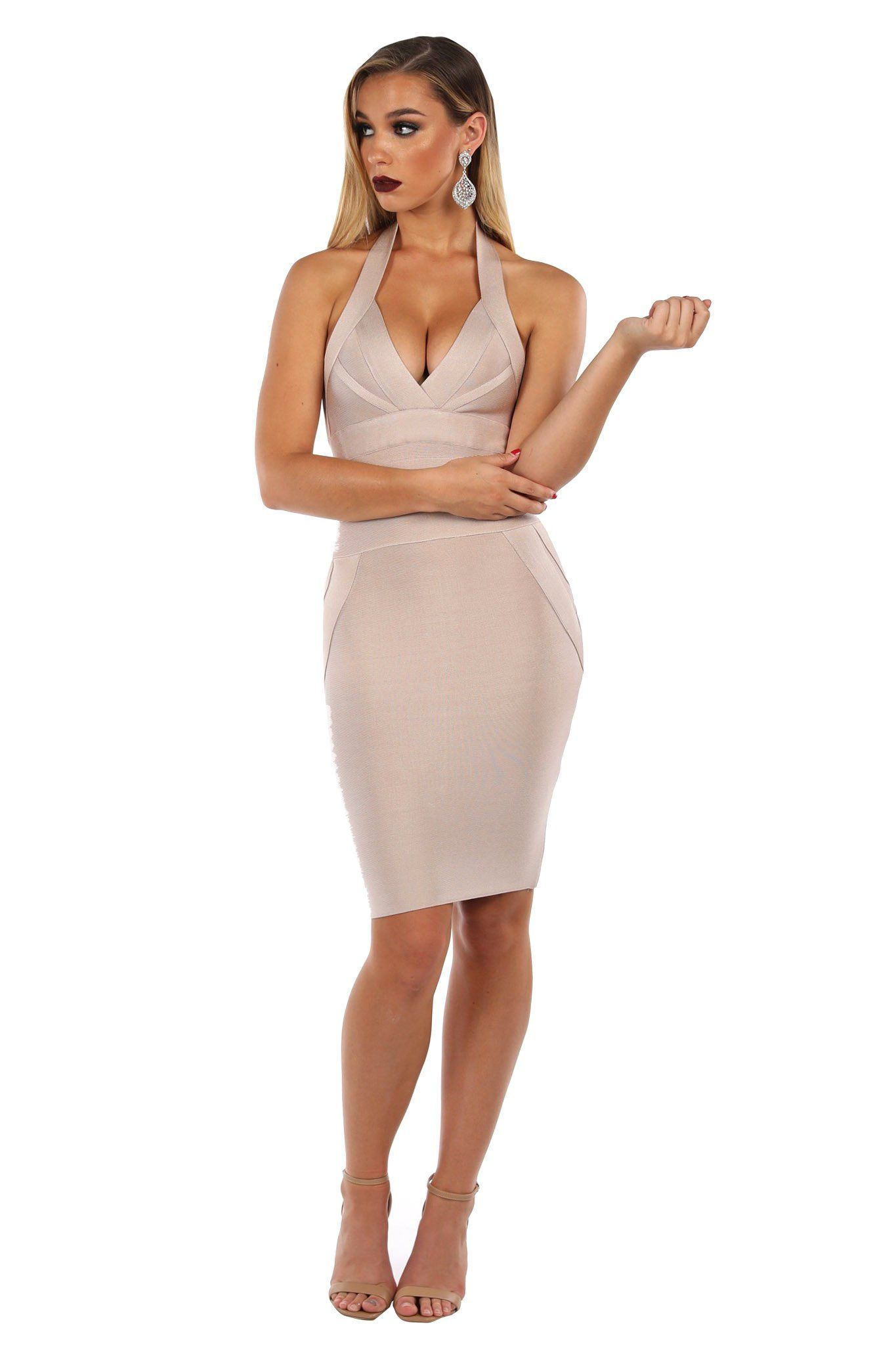 Nude colored tight fitting bandage dress in knee length with plunging halter neckline and open back design
