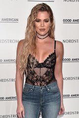 Khloe Kardashian wearing black sheer lace bodysuit with jeans