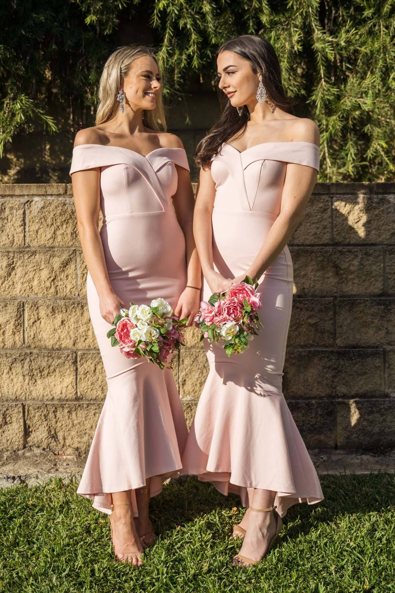 Blush pink maxi length bridesmaid dress with off-shoulder sweetheart neckline and high low fishtail hem