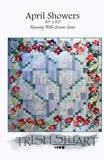 pattern cover shows the whole queen size strip pieced quilt with the fusible applique happy flowers bordering all four sides.