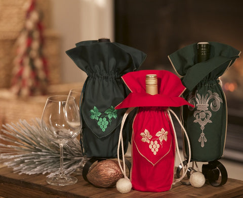 A Christmas gift set of a trio of wine gift bags with two showing grapes ready to be made into a fine wine and one showing the crown of a fine gift bag.