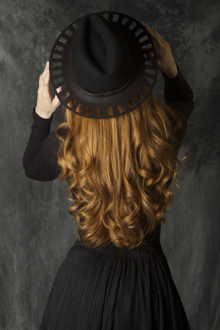 Leather brimmed trilby on tumbling ginger curls.