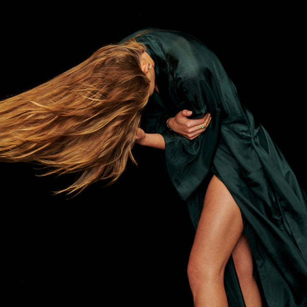Blonde Girl wearing Green Silk Kimono Robe leaning over and flipping her hair