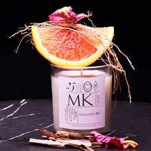 Load image into Gallery viewer, small candle on black marble with rose petals, wood chips, an orange wedge and dried vetiver
