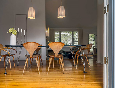 Dining room table surrounded by 6 modern wood chairs.