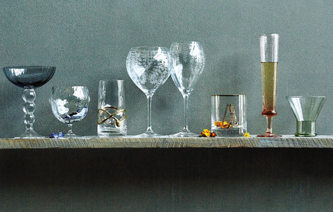 A variety of different shaped drinking glasses photographed on a shelf