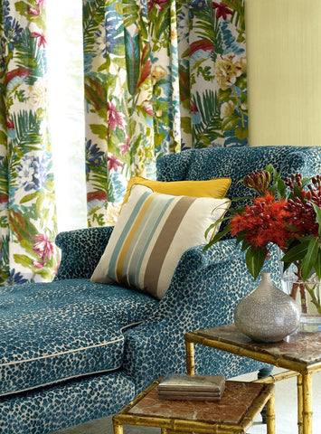 A vignette of a room with mixed patterns on the window treatments and chaise lounge.