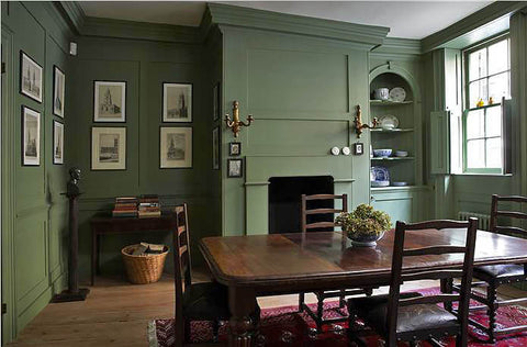 A primitive rustic-style dining area with walls and ceiling painted in Farrow & Ball's Calke Green.