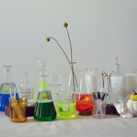 An assortment of vintage laboratory glass with different colored liquids inside.