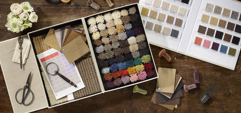 A sample kit photographed in flat lay style with scissors, wool rug samples, and color cards.