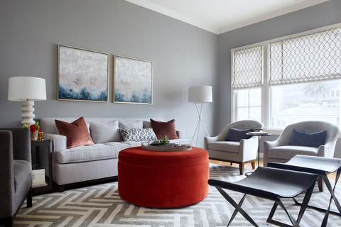 A large gray living room filled with mid century modern furniture, a gray sofa, and large red velvet ottoman in the center.