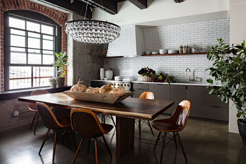Kitchen with a white tile backsplash and dining area featuring live edge wood table and 6 modern leather and metal chairs, plus a huge round glass chandelier by Ochre
