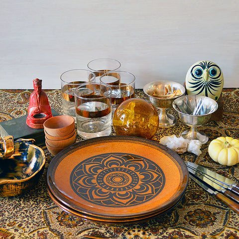 A Halloween style table setting with a brown plate, horn handled utensils, and small decorative pieces.