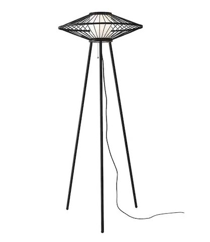 A black abstract style floor lamp on a tripod base with an oblong top of caged metal with a cylindrical linen shade in the center.