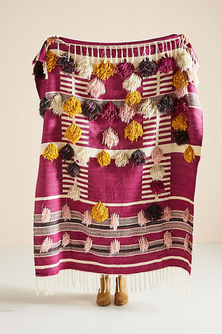 A handwoven pink throw blanket with brown and yellow tassels all over the front of it.