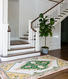 An Oriental-style pink and green rug laying at the foot of a grand staircase with a fiddle leaf fig tree off to the side.