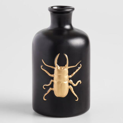 A short matte-black vase with a gold beetle pictured on a white background.