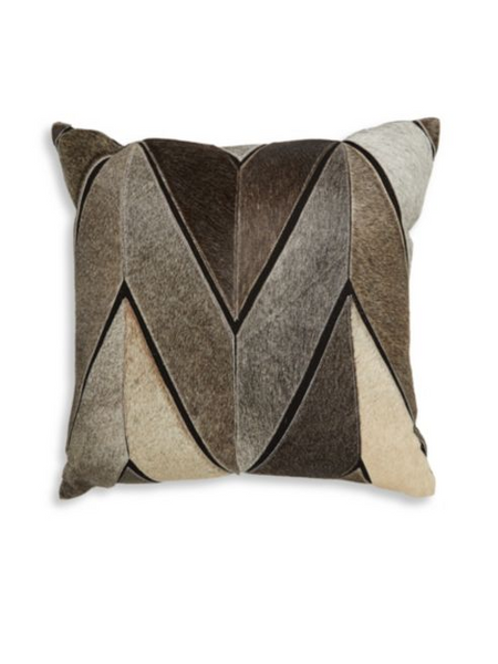 A throw pillow composed of different shades of brown calf hair sewn into a chevron pattern.
