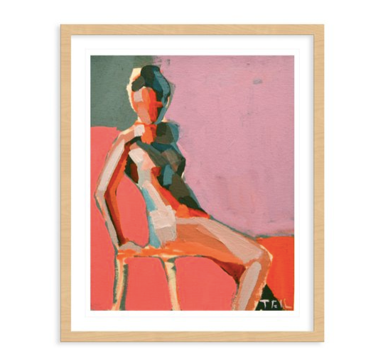 A framed print of a seated woman in the abstract style with a pink, orange, and green palette.