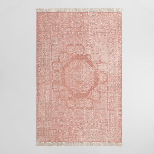A pink dhurrie-printed handmade rug with fringed sides on a white background.