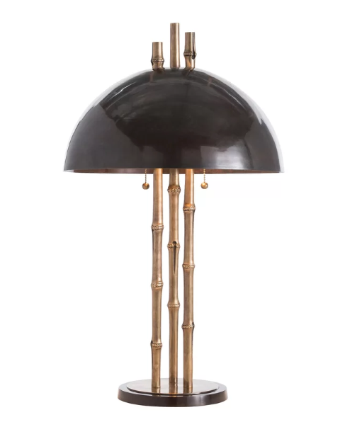 A table lamp with a glossy black shade and three stalks of brass faux bamboo stalks making up its base. Shot on a white background.