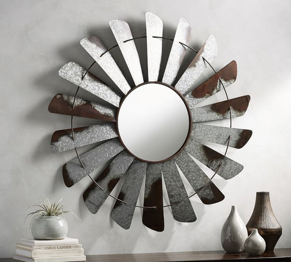 A round mirror set inside of galvanized windmill-style blades that are a tad rusted and industrial.