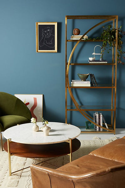 A tall, brass bookshelf with a semicircle motif going down the center, and positioned in a living area and styled with vases, decorative items, and books.
