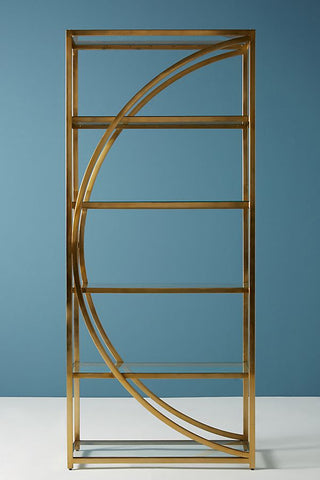 A tall brass bookshelf with a semicircle motif going down the middle.