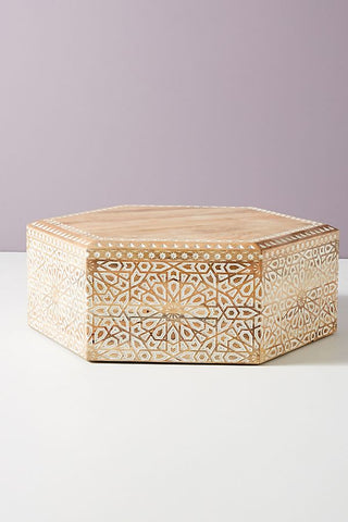 A hexagonal natural wood coffee table with inlaid designs. Has a global ethic feel.